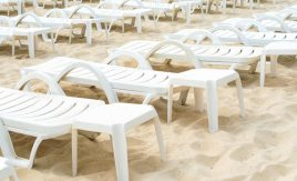 rows of empty lounge chairs on beach